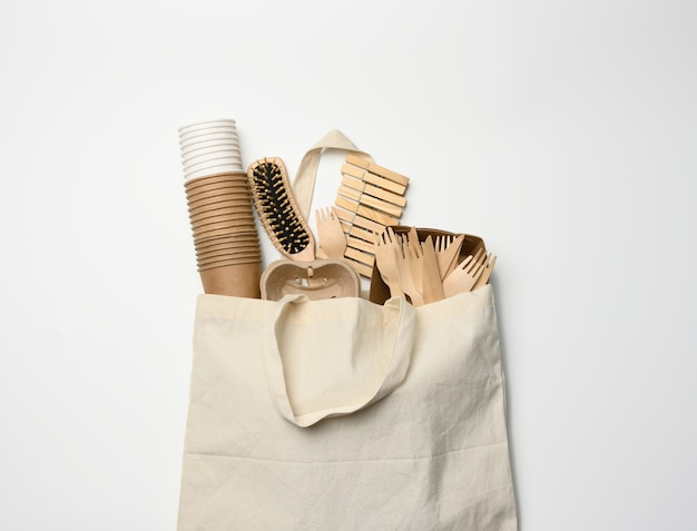 White textile bag and disposable tableware from brown craft paper on a white background. view from above, plastic rejection concept, zero waste