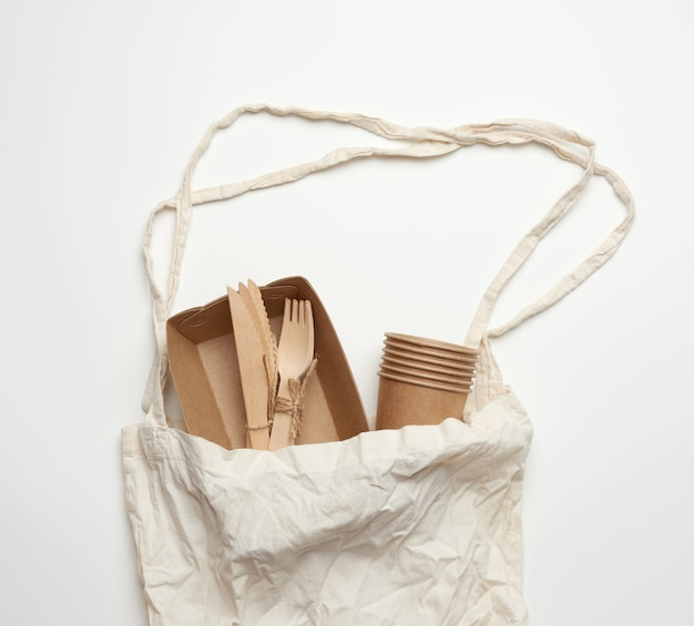 White textile bag and disposable tableware from brown craft paper
