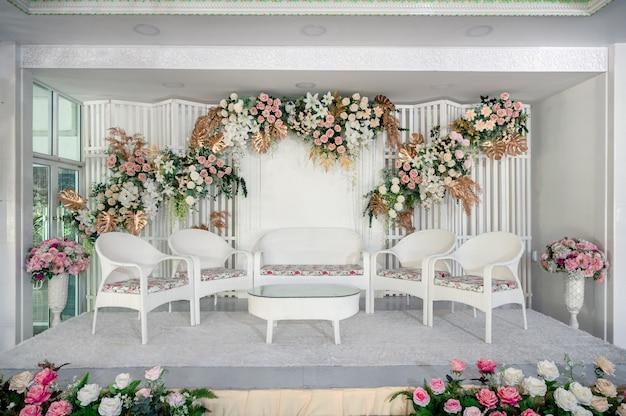 Белая тема оформления свадебной сцены с яркими цветами и стулом для гостя в традиционном азиатском браке