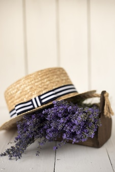 On white there is a wooden basket with a fragrant fresh bouquet of olive lavender on it lies a charming hat.