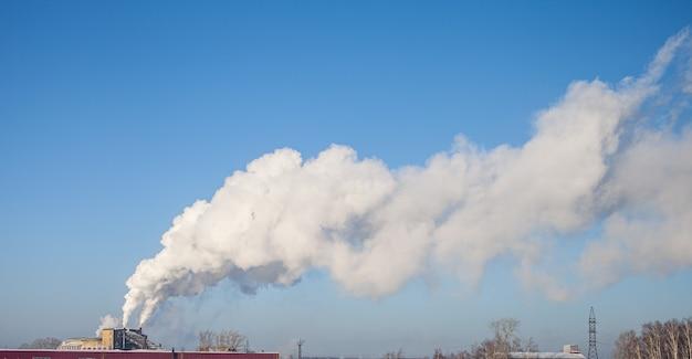 Белый густой дым из дымохода котельной промышленной зоны