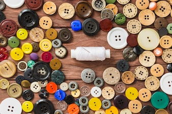 White thread and needle surrounded by many colorful buttons