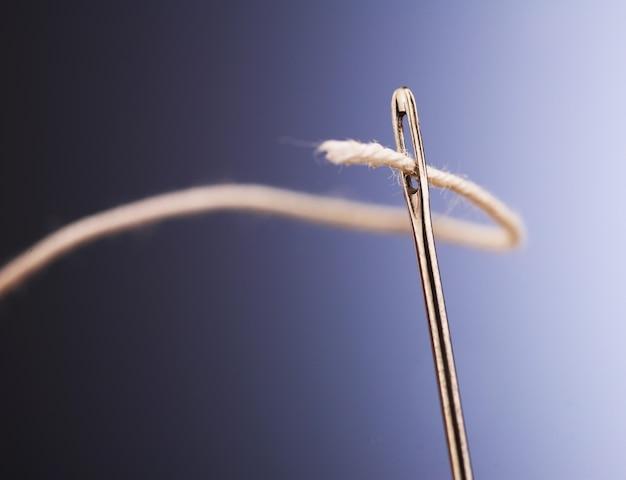 白い糸が針の目を通り抜ける、クローズアップ