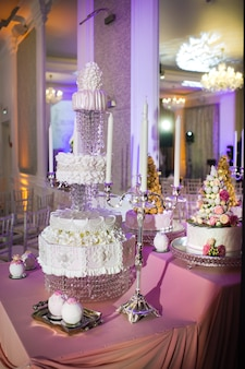 White three tiered wedding cake decorated with cream flowers on a stand.