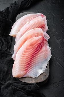Филе белой рыбы тилапии на черном столе
