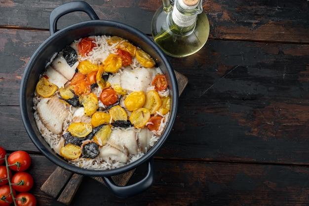 バスマティライスとチェリートマトと白いティラピアの魚、暗い木製の背景、テキストのコピースペースと上面図
