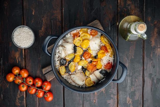 バスマティライスとチェリートマトと白いティラピアの魚、暗い木製の背景、上面図