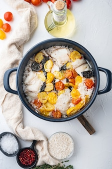 バスマティライスとチェリートマトと白いティラピアの魚、白いテーブル、上面図
