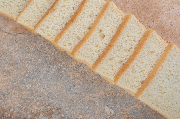 Fette di pane tostato bianco su sfondo di marmo