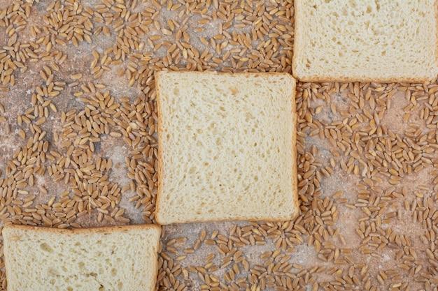 Fette di pane tostato bianco con orzo su fondo di marmo