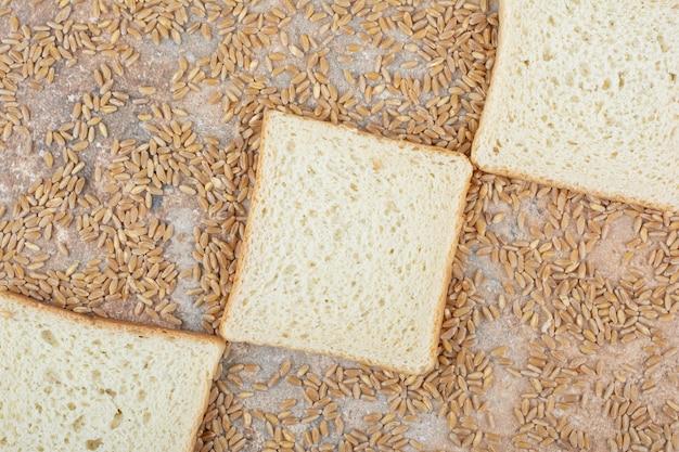 Fette di pane tostato bianco con orzo su superficie di marmo