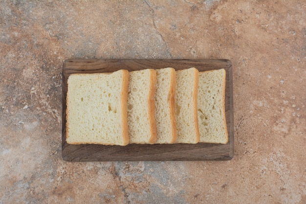 White toast slices on wooden board