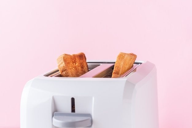White toaster with roasted bread on pink background