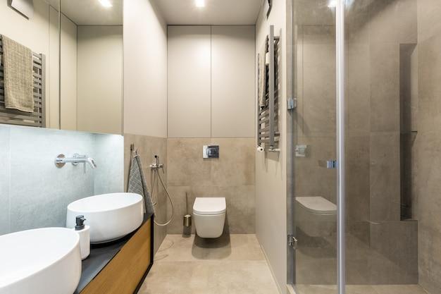 洗面台付きのモダンなバスルームインテリアのベージュの壁に白いトイレ。本物の写真