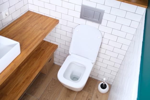 開いたふたが浴室の背景に立っている白い便器