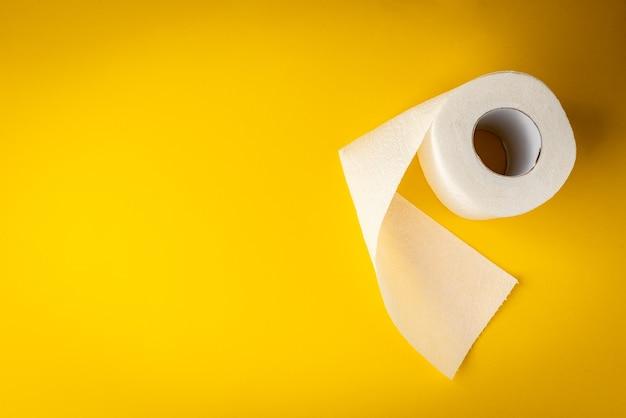 Белая туалетная бумага на желтом фоне.