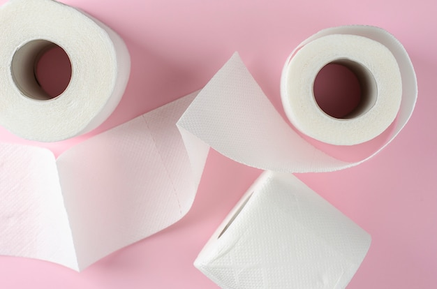 White toilet paper rolls on pastel pink