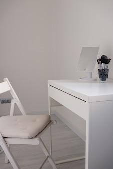 Белый туалетный столик с зеркалом и кистями для макияжа на белой поверхности в современном интерьере комнаты
