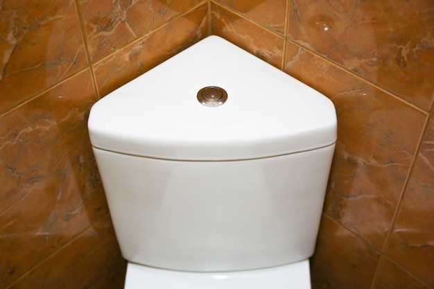 White toilet tank in the triangle shape. bathroom in the hotel or at home.
