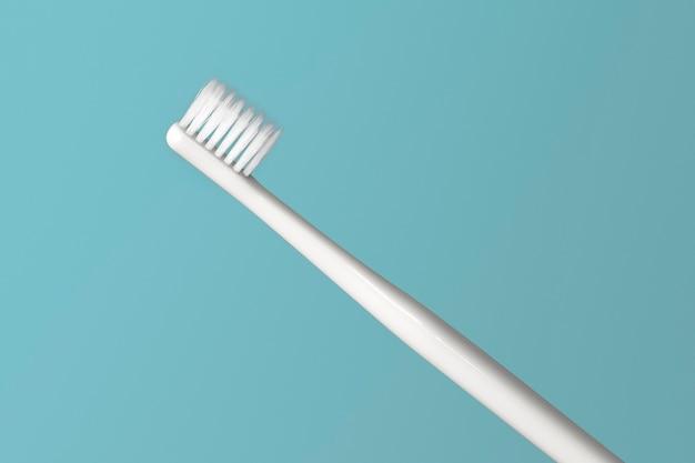 Белая зубная щетка на зеленом фоне