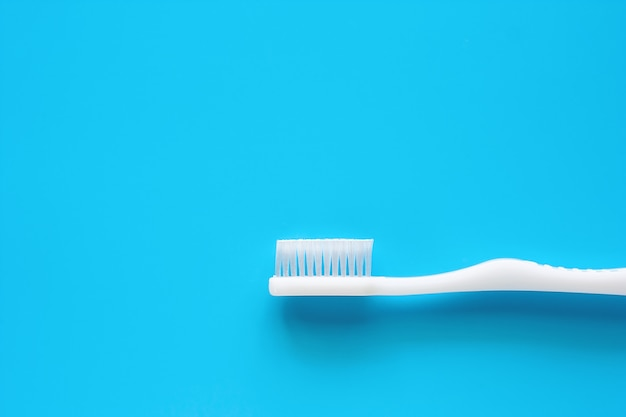 White toothbrush used for cleaning the teeth on blue background