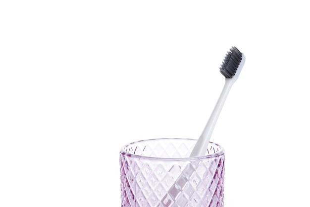 Белая зубная щетка с черной щетиной в стеклянном стакане, изолированном на белом
