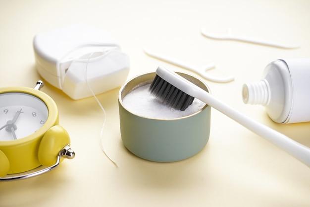 Белая зубная щетка с зубным порошком на желтом