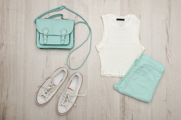 White top, mint-colored jeans, white sneakers and handbag