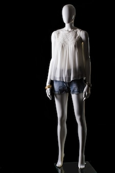 Белый топ, шорты и аксессуары. женский манекен в повседневной одежде. стильная одежда для барышень. привлекательные цены в бутике.