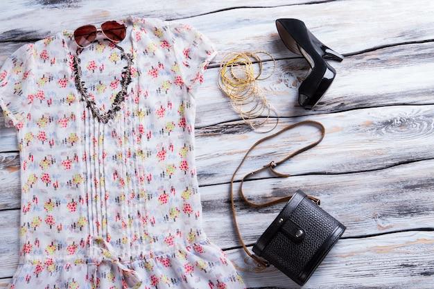 화려한 패턴의 화이트 탑. 여성용 상의, 신발, 지갑. 여성을 위한 트렌디한 여름 룩. 액세서리와 함께 고품질 의류.