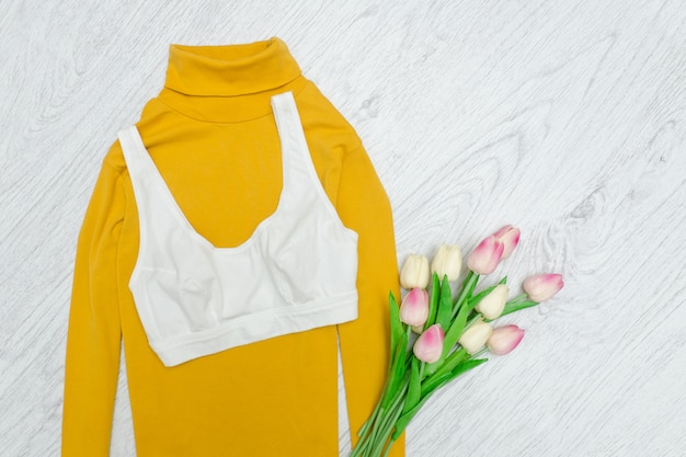 White top on yellow turtleneck. pink tulips. fashionable concept.