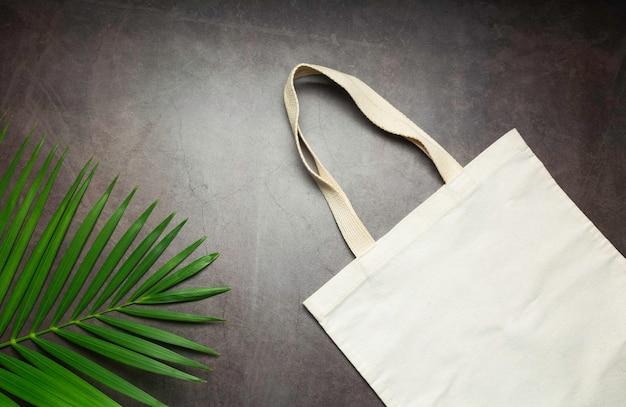 ホワイトトートバッグキャンバス生地。コピースペース付きの洋服ショッピングサックのモックアップ。