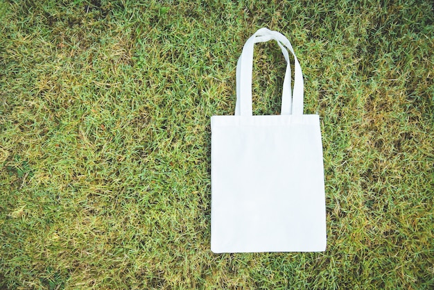 White tote canvas fabric eco bag cloth shopping sack on green grass background / zero waste use less plastic say no plastic bag pollution problem