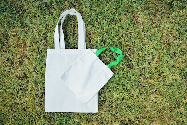 White tote canvas fabric eco bag cloth shopping sack on green grass