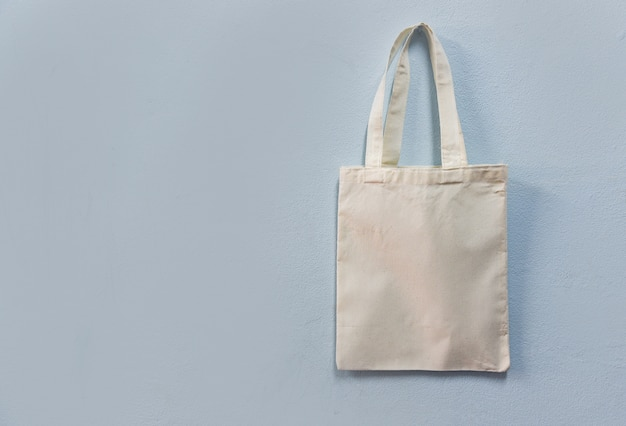 White tote canvas fabric eco bag cloth shopping sack on wall background