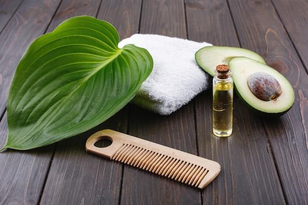 Белое полотенце, авокадо, маленькая стеклянная бутылка и деревянная расческа для волос лежат на деревянном столе