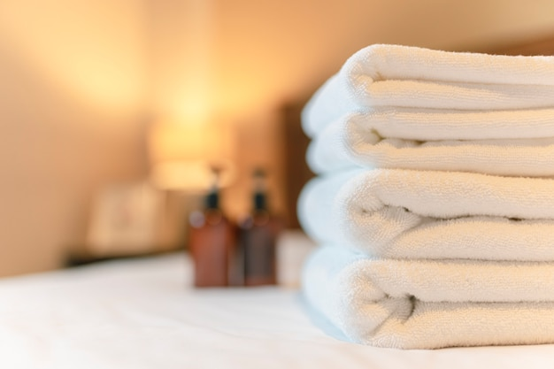 White towel on bed in guest room for hotel customer. towels  in spa or fitness center.