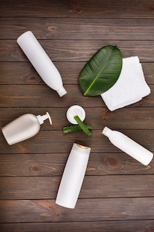 White towel, bottles of shampoo and conditioner lie on a table with green leaf and aloe