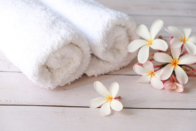 A white towel is placed on the table, with flowers on its side.