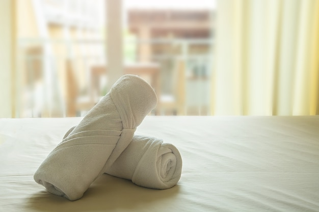 White towel roll cream rolls on yellow cotton mattresses with soft light in morning.