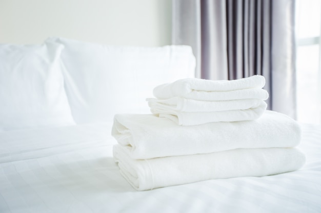 White towel on white bed in bed room