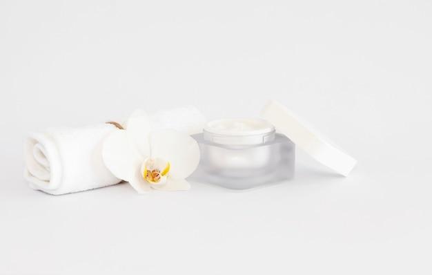 白いコピースペースの背景に白いorñ隠された花とフェイスクリームと白いタオル。フェイシャルトリートメントのコンセプト。