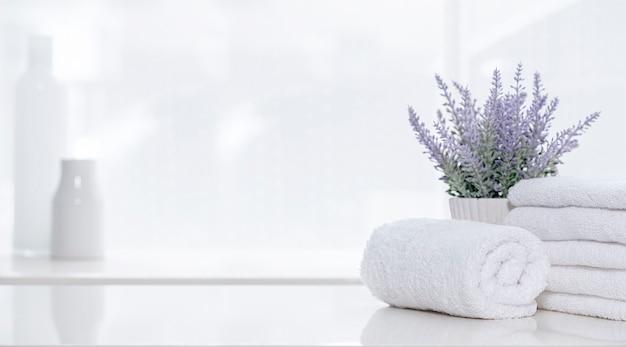 Белые полотенца и комнатные растения на белом верхнем столе