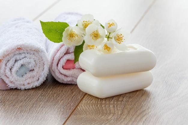 浴室の手順のための白いタオルと石鹸と木の板上のジャスミンの花。スパ製品とアクセサリー