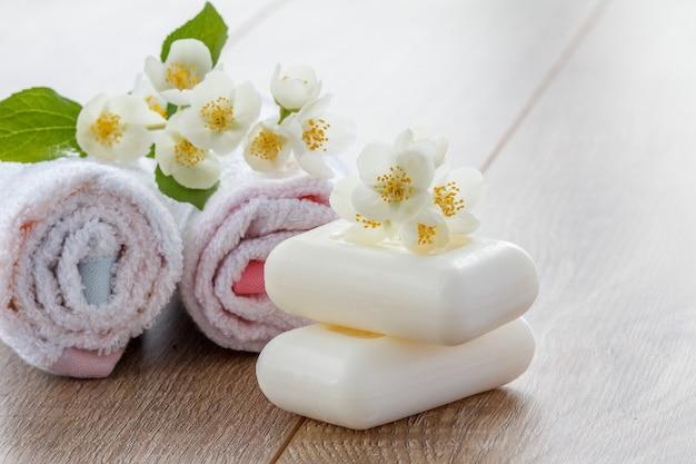 木の板にジャスミンの花で飾られたバスルーム用の白いタオルと石鹸。スパ製品とアクセサリー