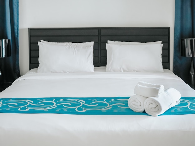 White towels on bed decoration in bedroom with pillows.