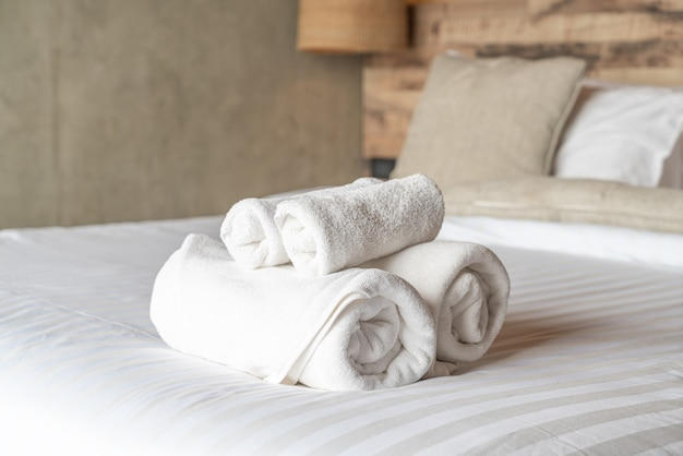 White towels on bed decoration in bedroom