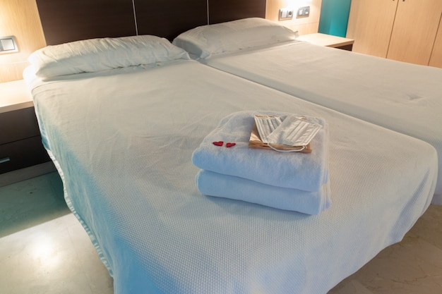 White towels folded at the foot of a hotel bed with a mask and protective gloves detail of two red hearts copy space
