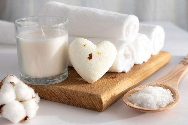 하얀 수건은 나무 쟁반, 하얀 촛불 및 문지르는 소금에 롤러로 접혔습니다. 심장 모양의 목욕 공입니다. 배경이 흰색입니다. 스파 개념. 청결의 개념.