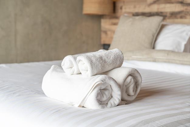 Белые полотенца на украшении кровати в спальне